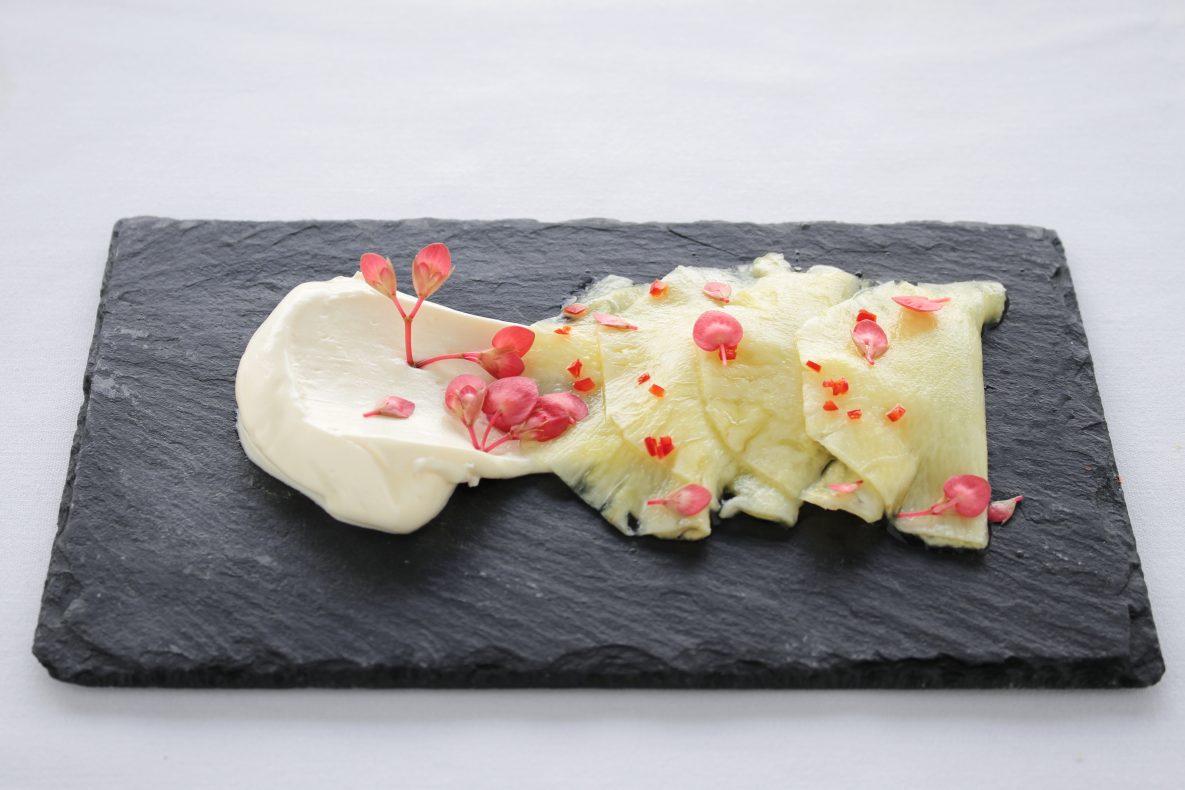 Dessert med ananas og blomster.