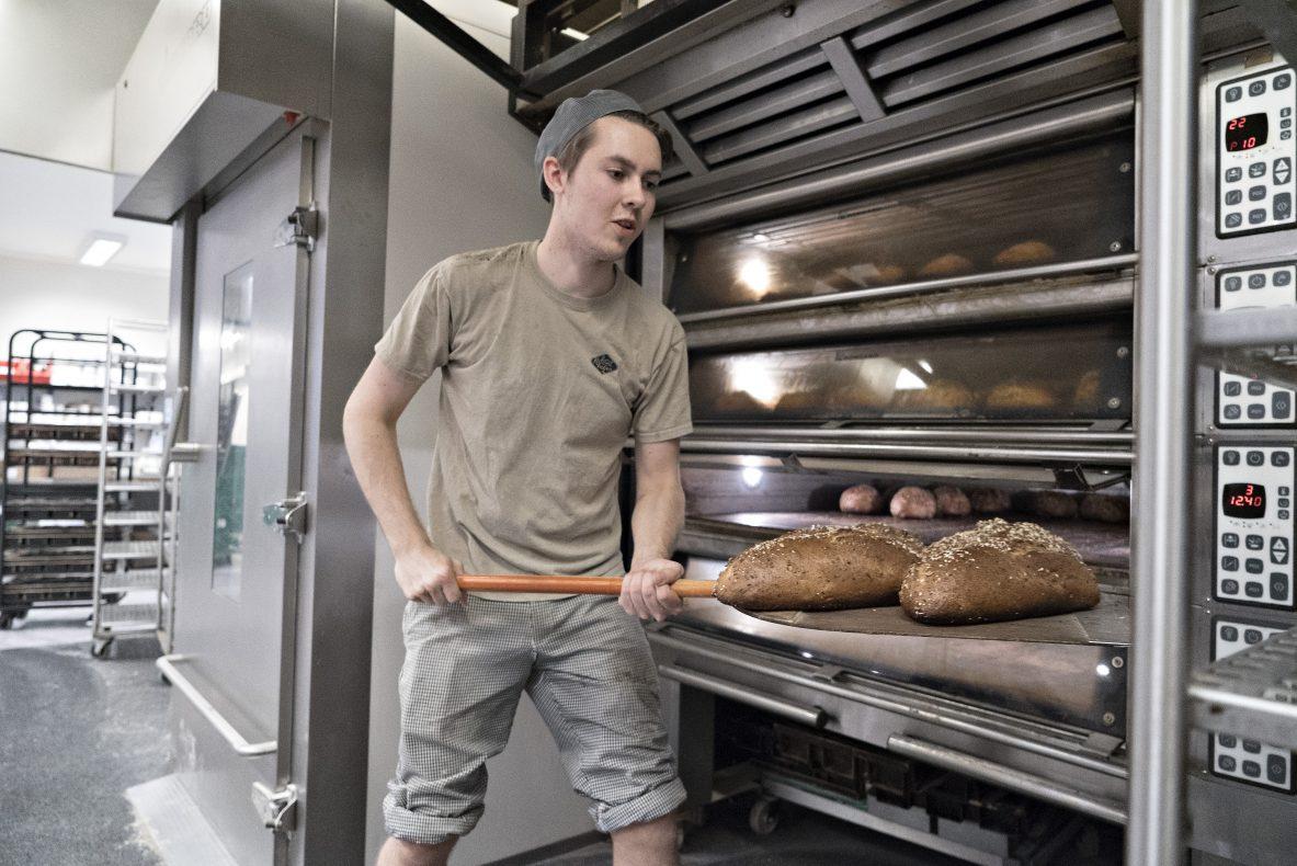 Baker i Kolonihagen Bakeri, Marius Lysø tar ut ferdigstekt hirsebrød av ovnen.