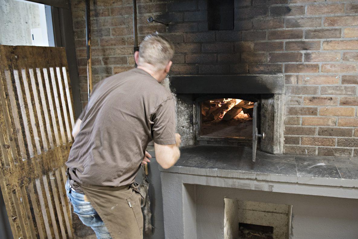 Baker Emil Lysø sjekker temperaturen i steinovnen. Ovnen er i drift hver dag, hele uken.