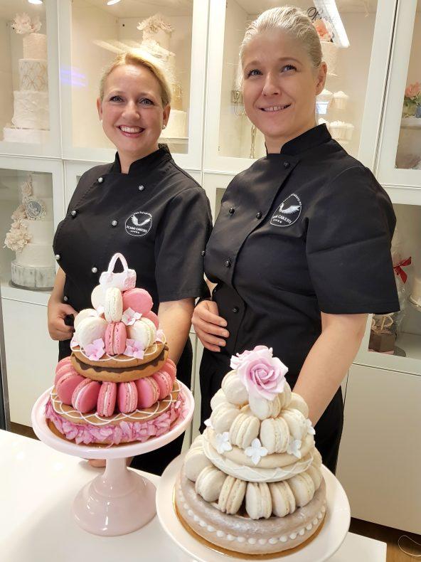 Kate Kippersund og Elisabeth Vikøren med to eksemplarer av den nye kaken, Flying Macaron Rings.