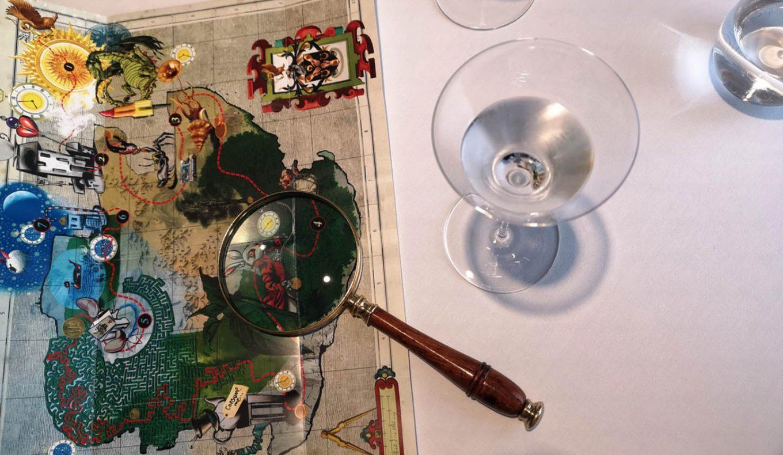 Ved bordene ligger et kart av en øy med en «reiserute». Ideen er å spiser seg igjennom kartet.