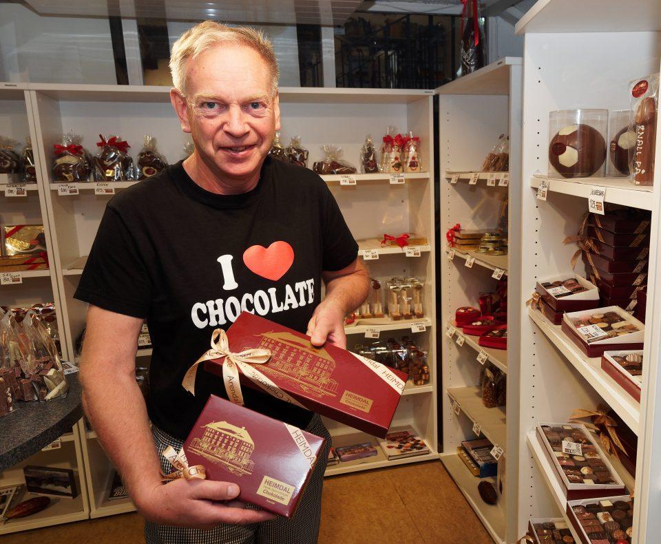 De klassiske konfekteskene prydes av Arendals gamle rådhus. I tillegg selger Morten Arnesen konfekt under gjennomsiktig lokk – mange kunder foretrekker det i dag.